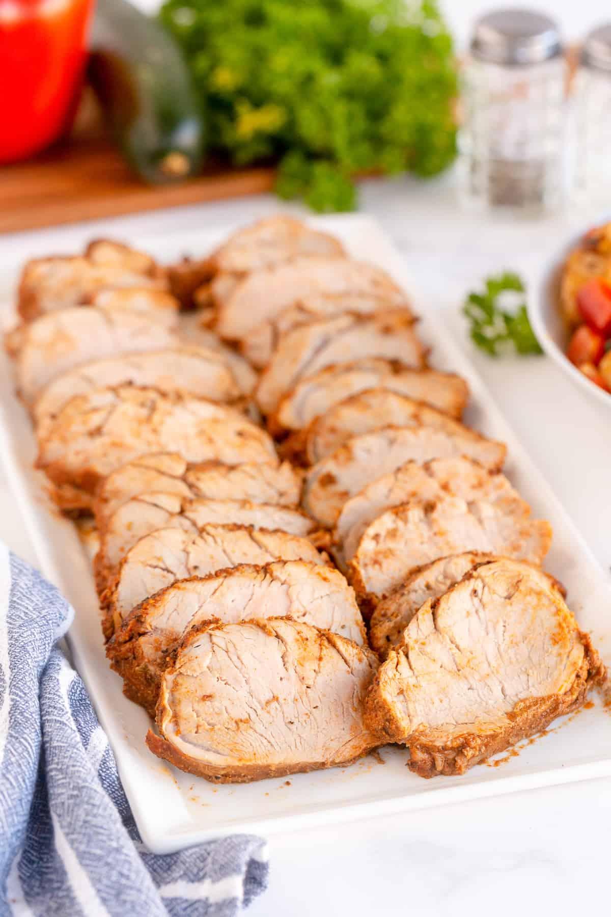 Sliced pork tenderloin on a serving platter.