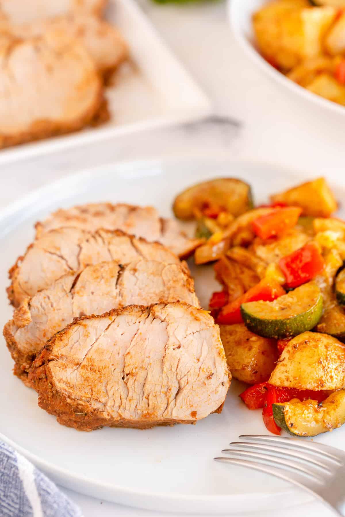 Sliced pork tenderloin and vegetables on a white plate.