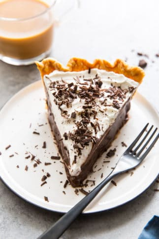 A slice of chocolate pie on a white plate with a fork.