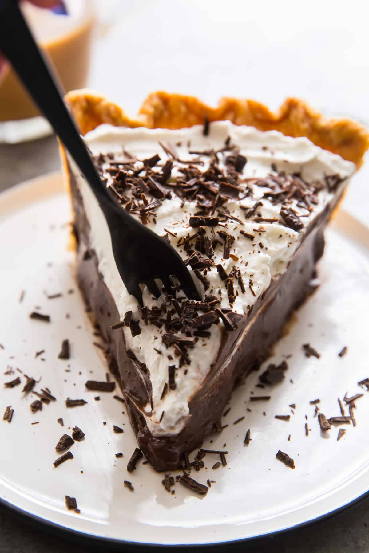 A fork breaks into a slice of chocolate cream pie.