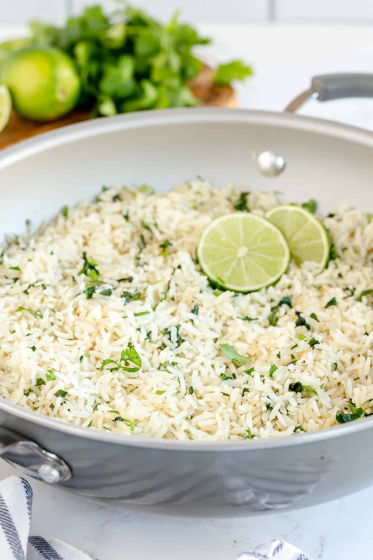 A skillet filled with white rice, cilantro and lime slices.