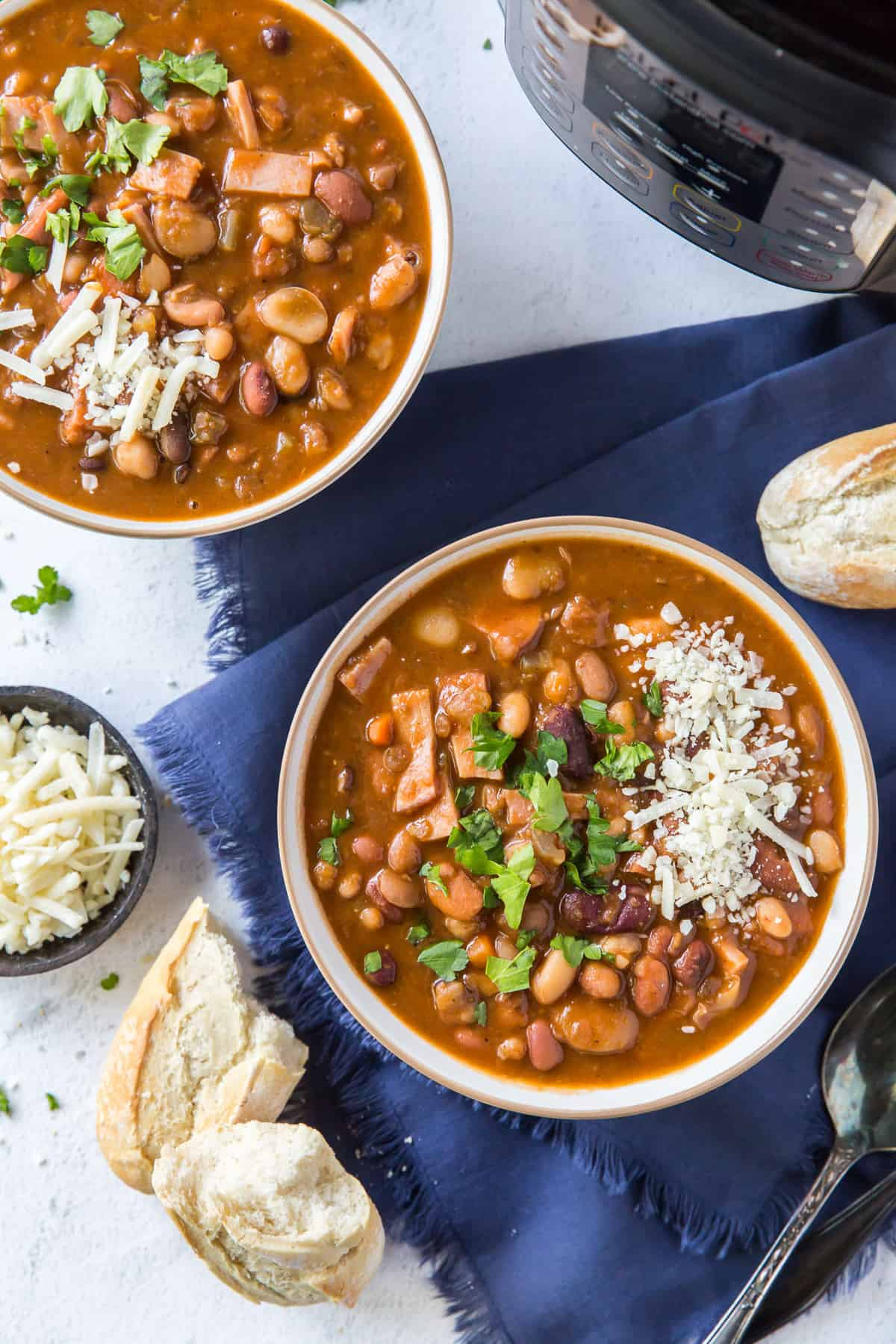Two bowls of bean soup in front of an Instant Pot.