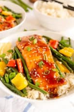 Salmon and vegetables on top of rice in a bowl.