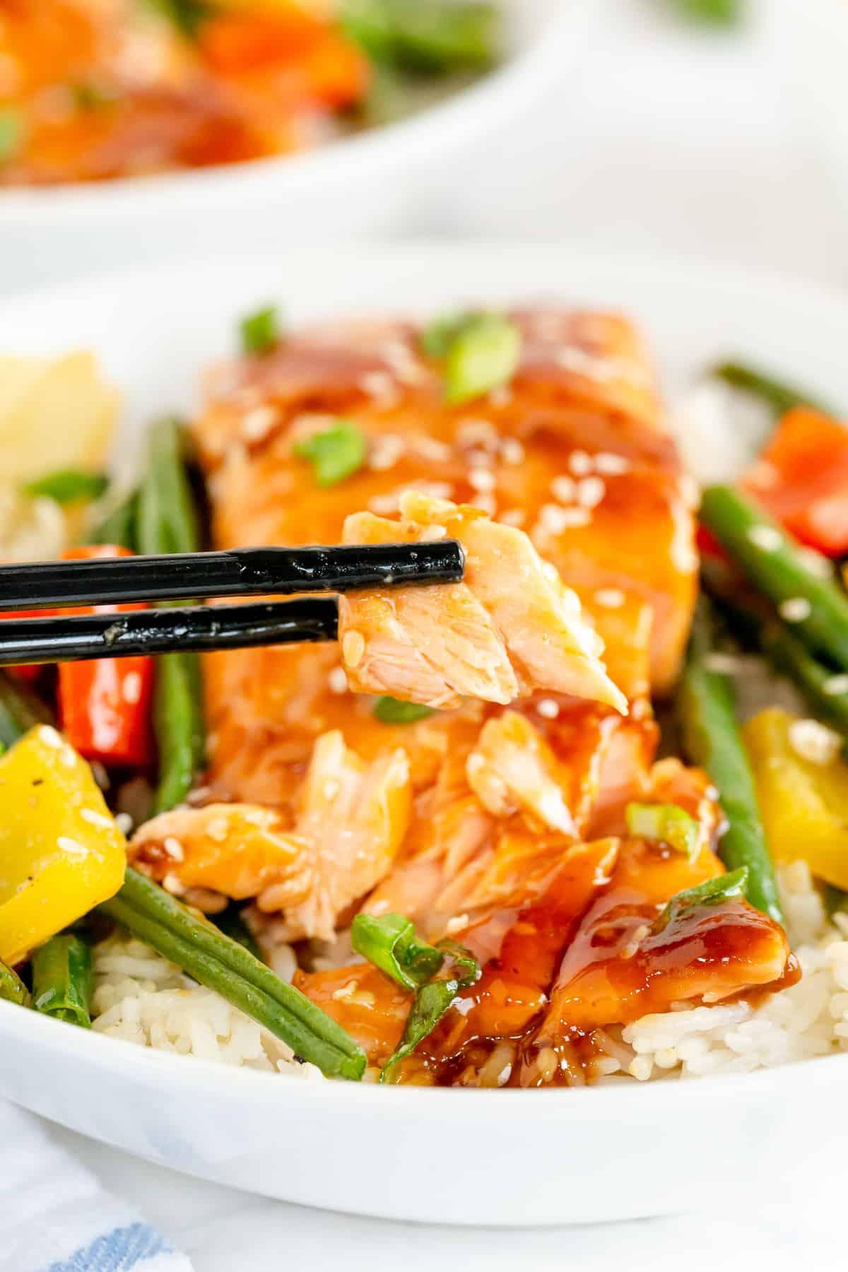 Chopsticks lift a piece of salmon.