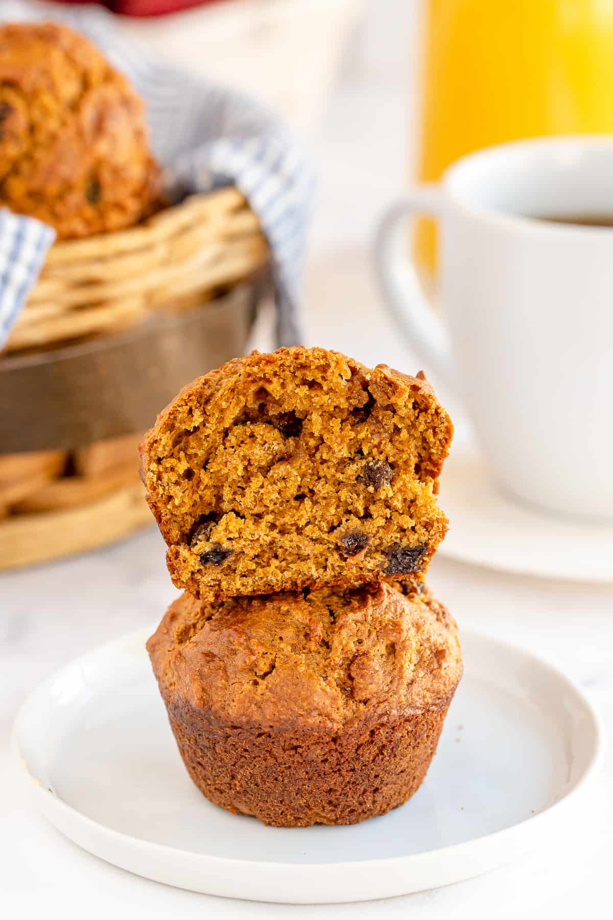 A bran muffin with a bite missing stacked on top of another.