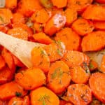A close up of carrots with dill in a skillet with a wooden spoon.
