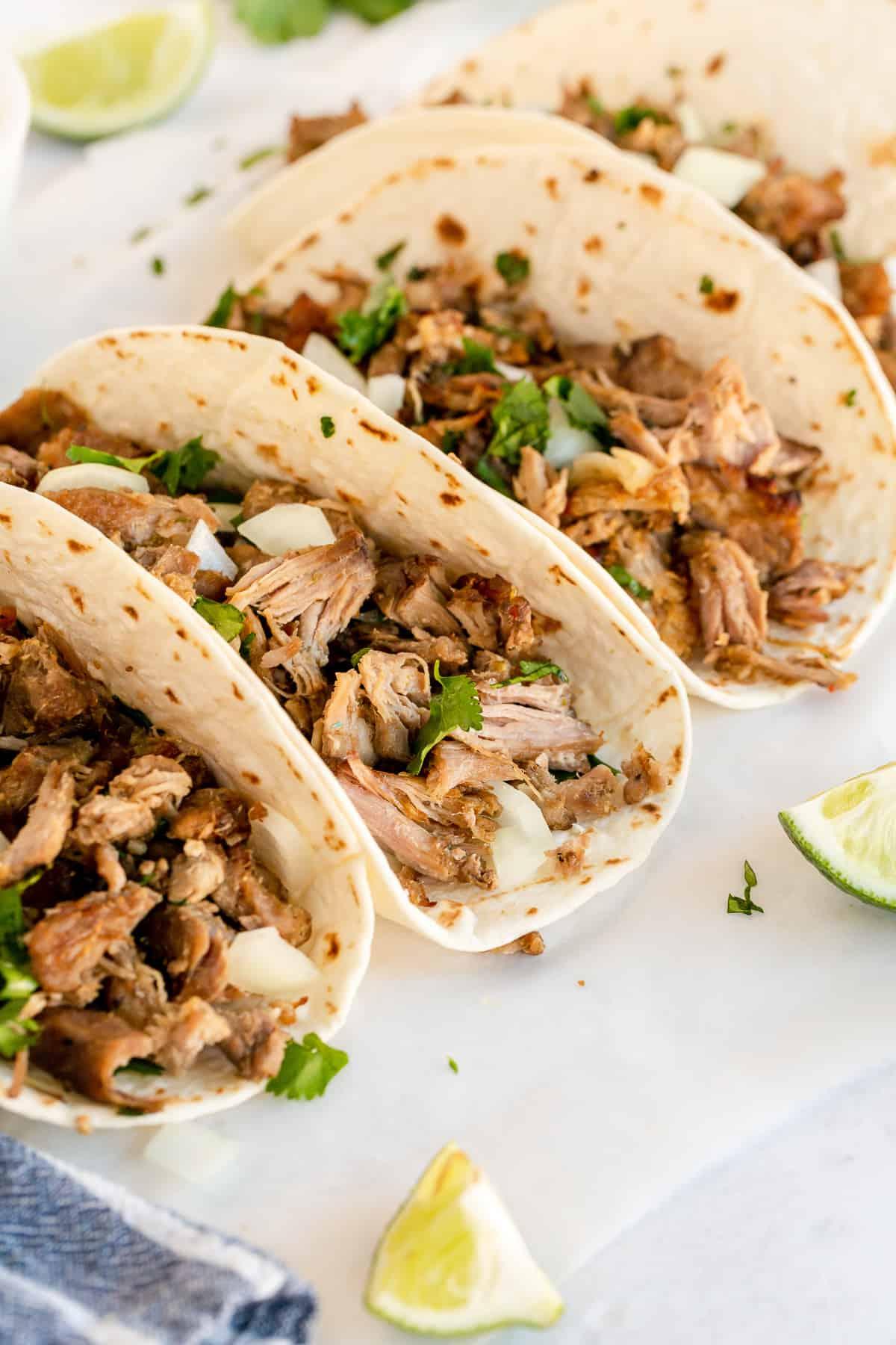 Three carnitas tacos on a platter.