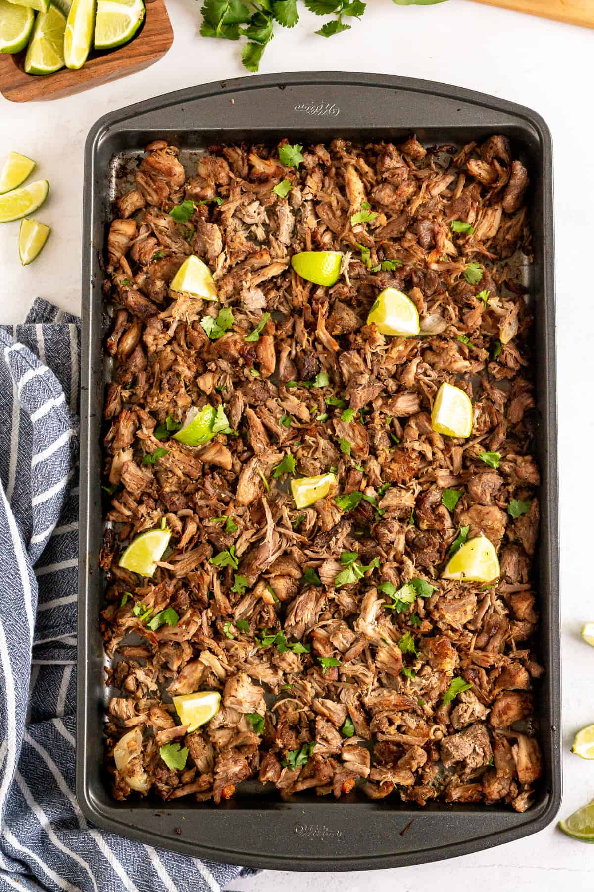 A baking sheet filled with carnitas and pieces of lime.
