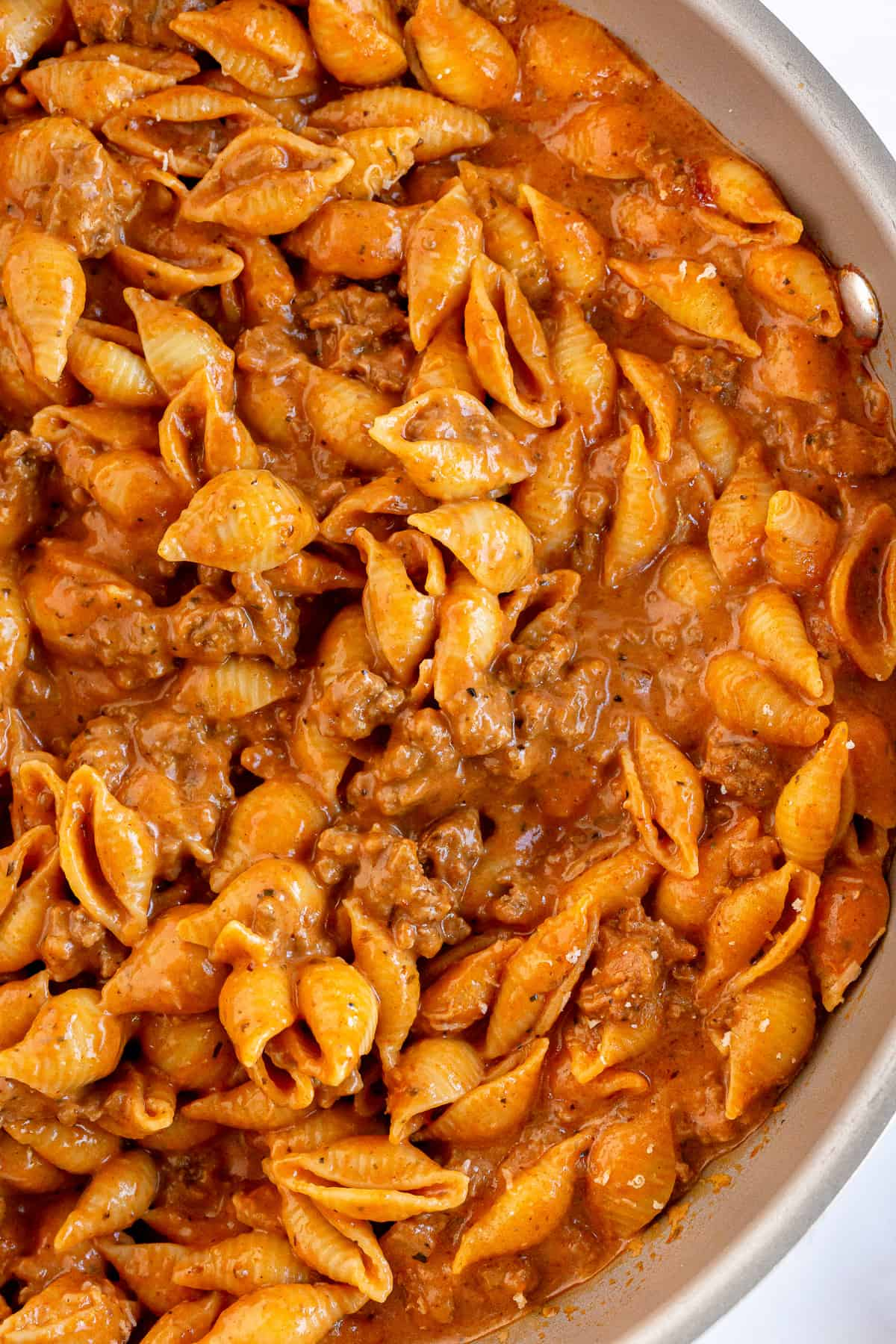 A closeup of a skillet full of pasta shells with a creamy sauce and ground beef.