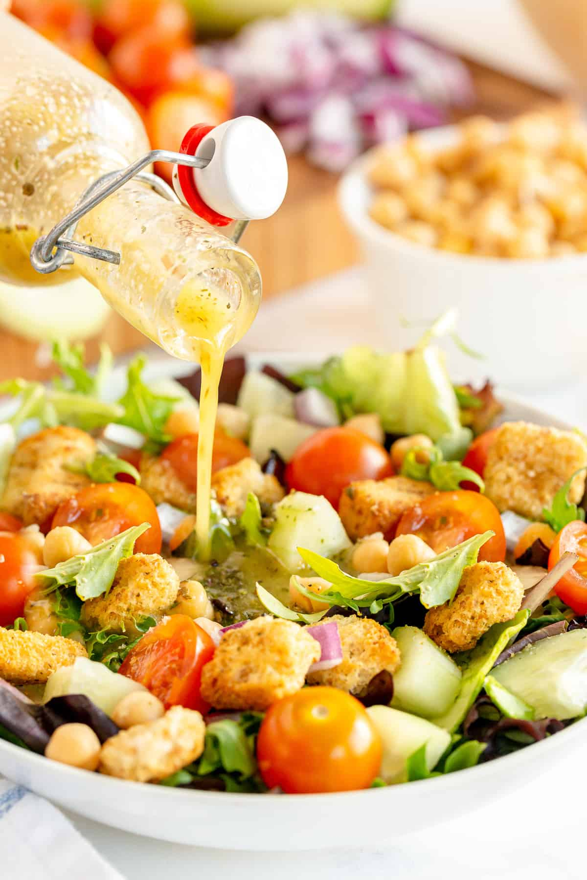 Homemade Italian Salad Dressing pours on to a colorful salad.