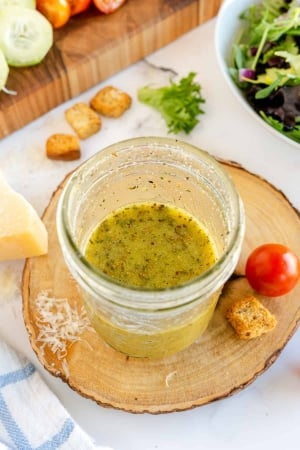 A mason jar filled with Italian Salad Dressing on a wood block.