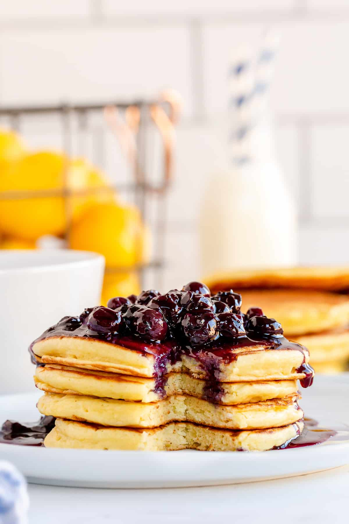A stack of pancakes topped with blueberry sauce with lemons in the background.