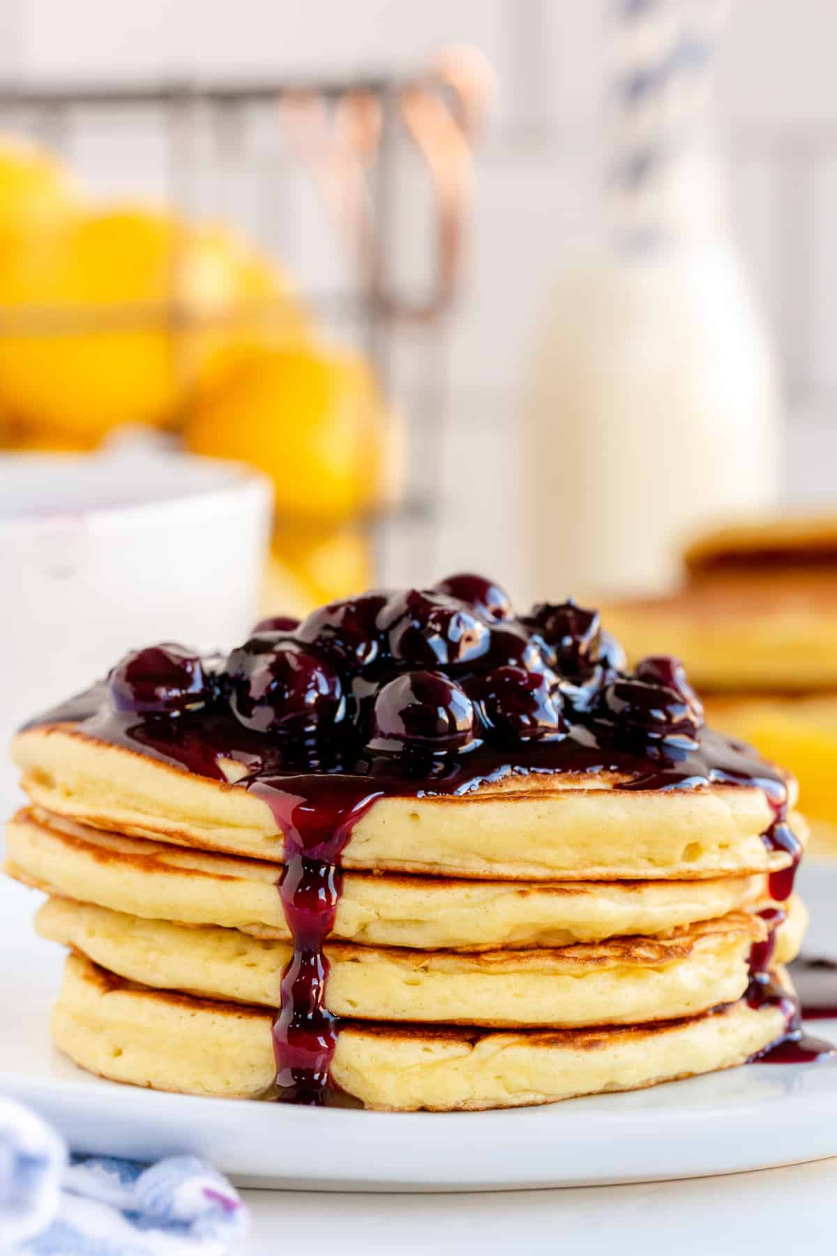 A stack of pancakes with blueberry sauce running down the sides.