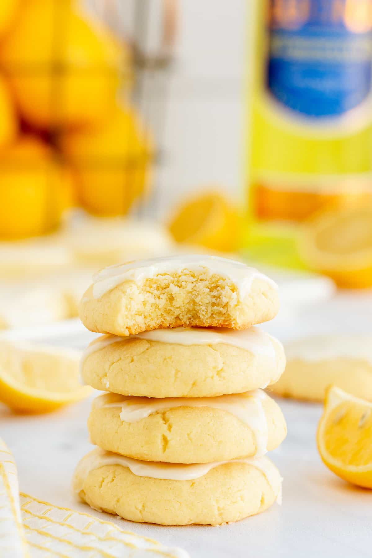 A stack of lemon cookies with a bite missing from the one on top.