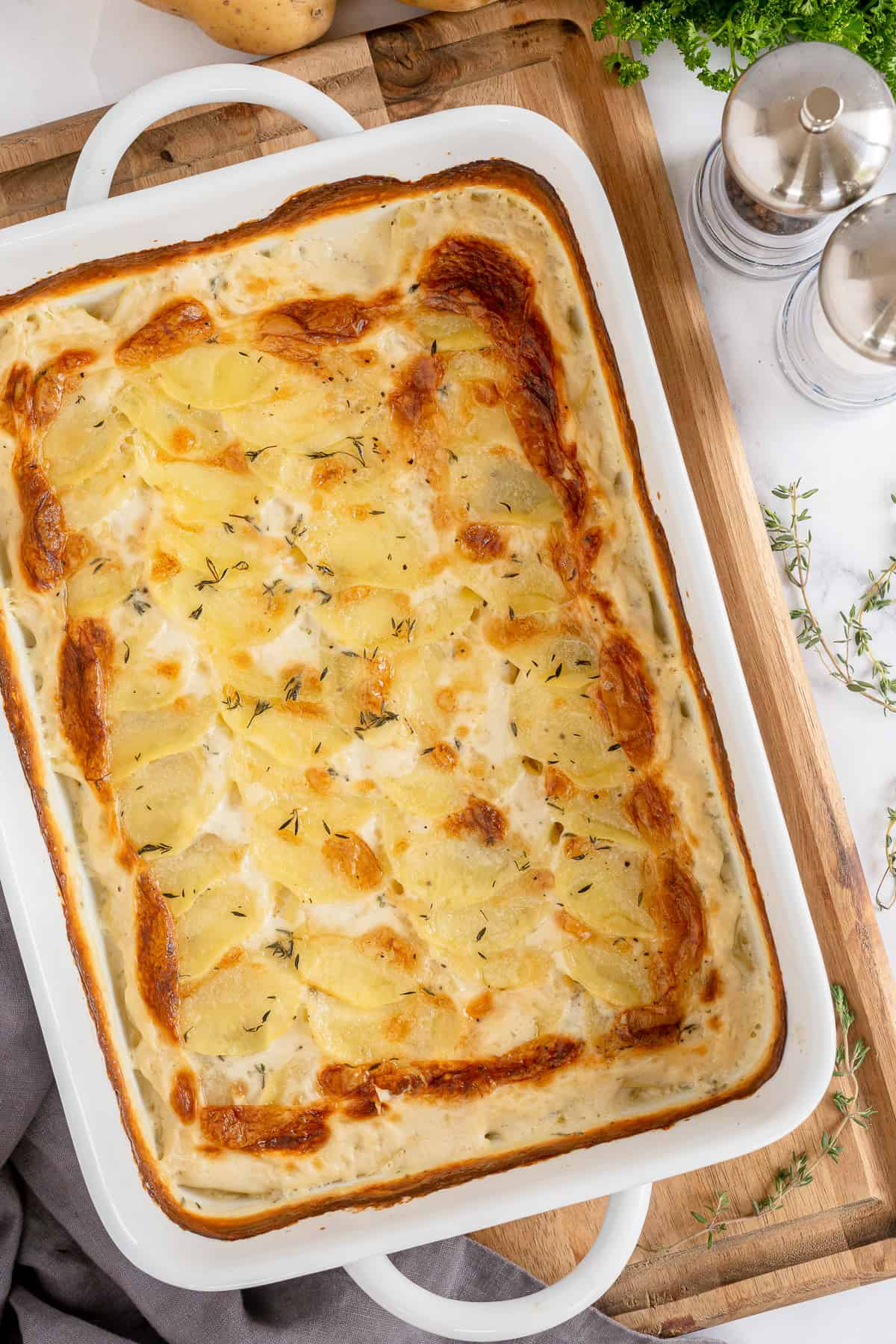 A casserole dish of Scalloped potatoes resting on a cutting board.