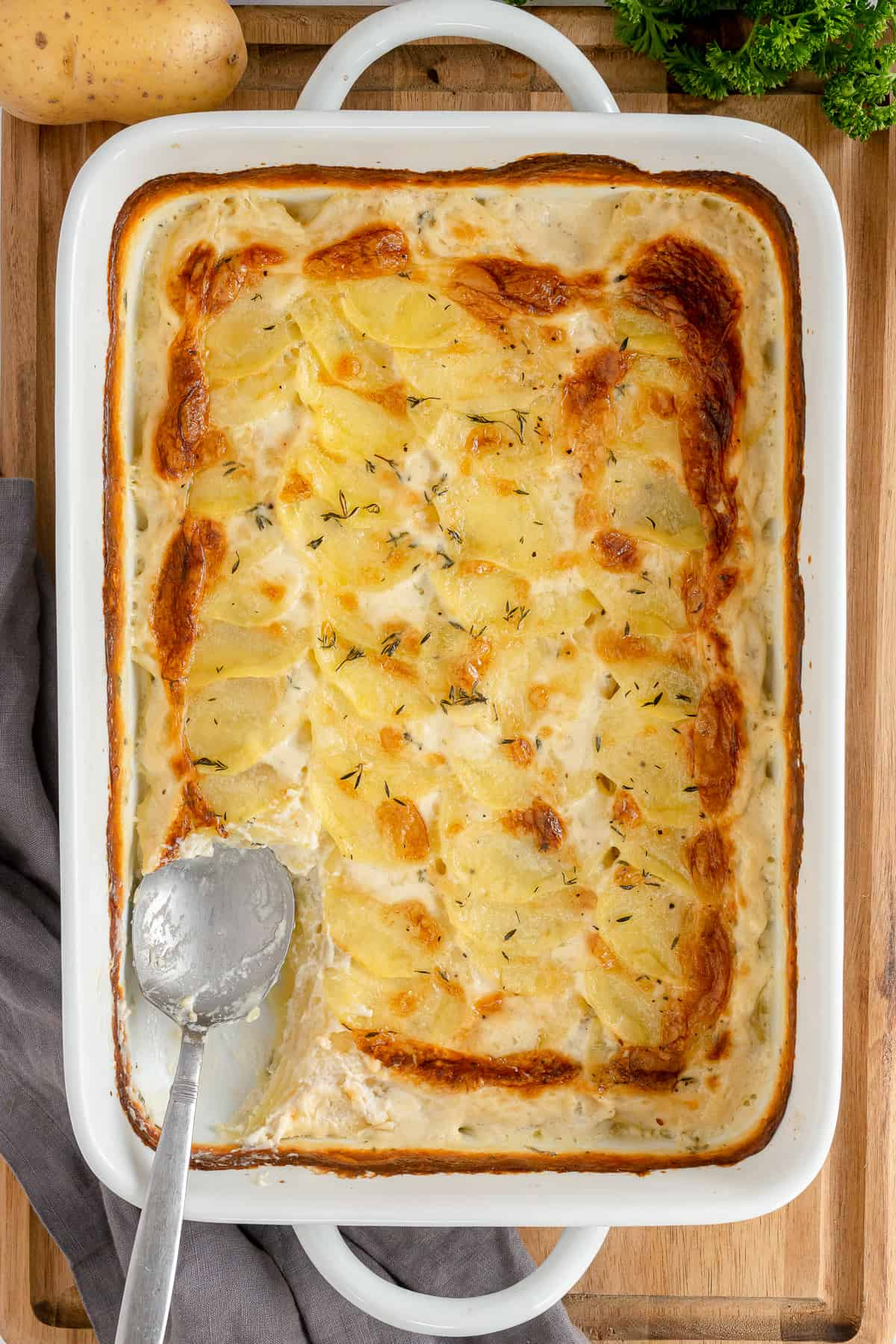 A spoon resting in a casserole of scalloped potatoes shot from over the top.