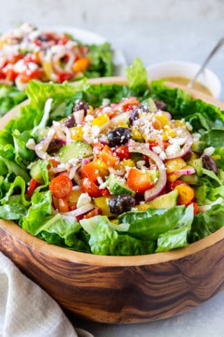 Greek Salad with tomatoes, onions, and kalamata olives in a wooden bowl.