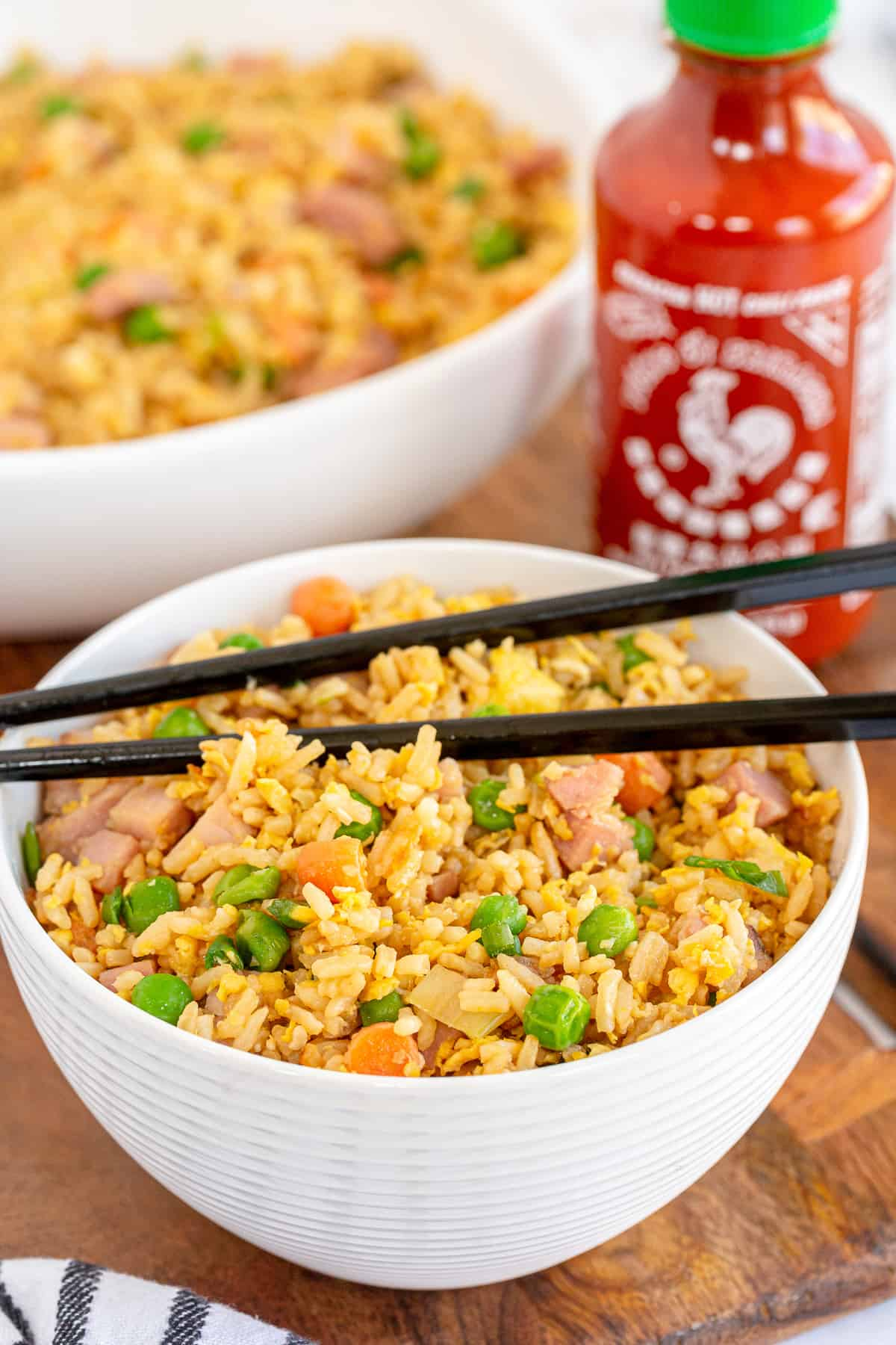 A bowl of fried rice with a bottle Sriracha behind it.