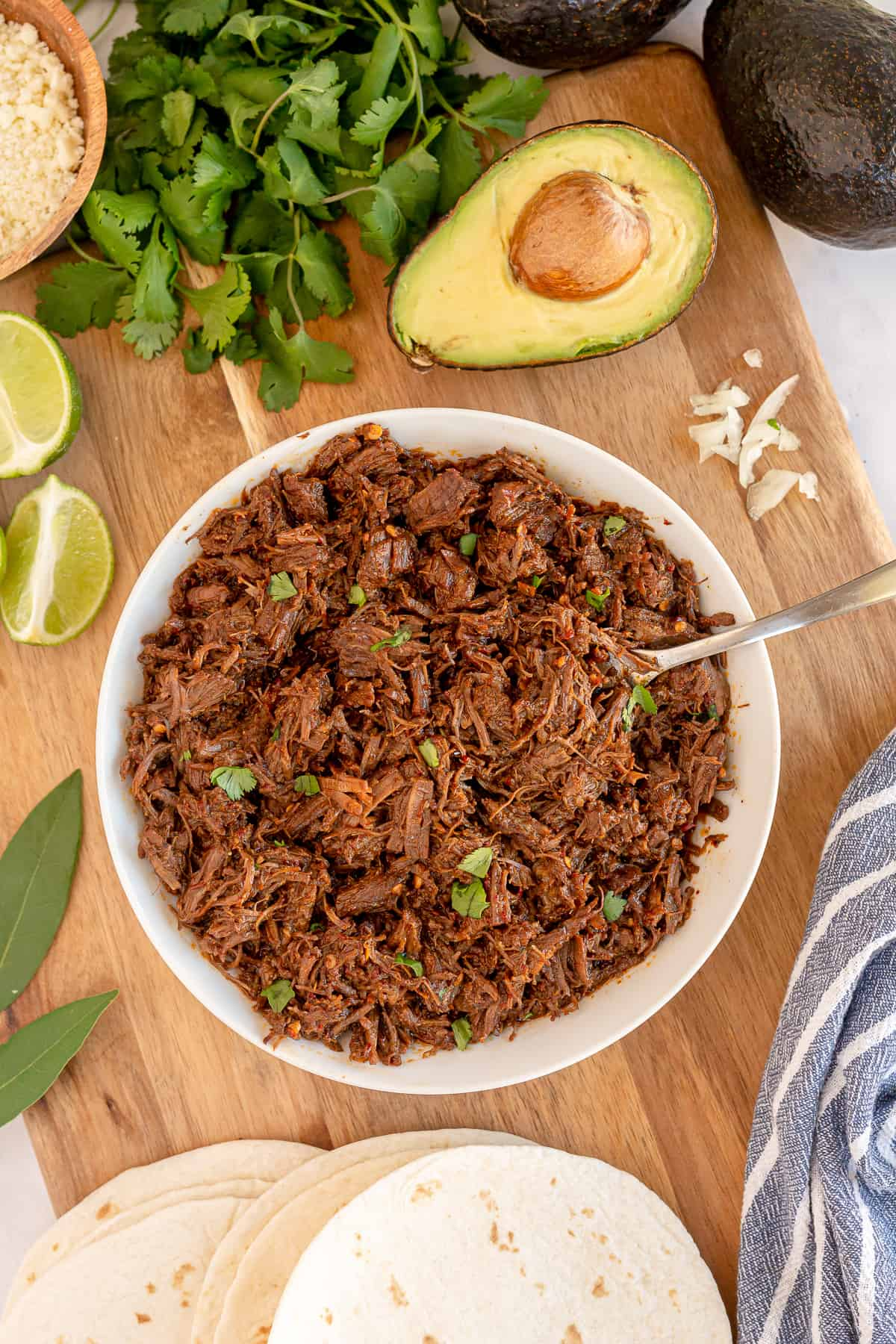 A bowl of Instant Pot Beef Barbacoa on a cutting board with other ingredients.