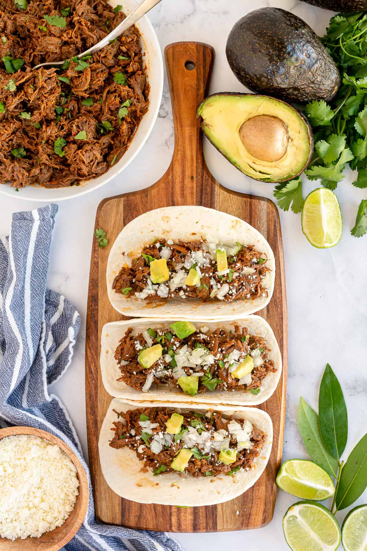 Three soft tacos on a cutting board shot from over the top.