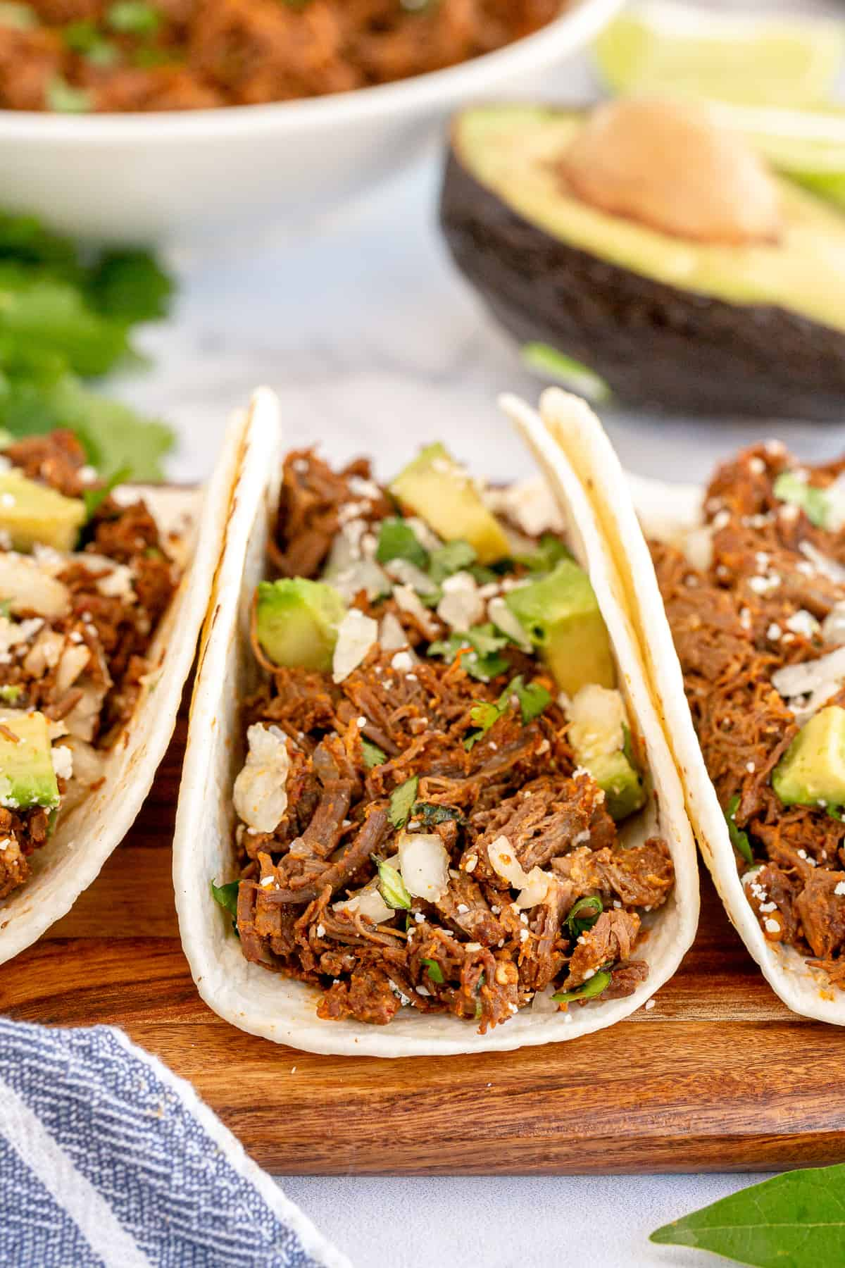 Three barbacoa tacos on a cutting board shot from the side.