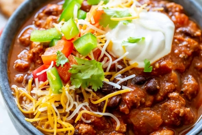 A bowl of chili loaded with toppings.