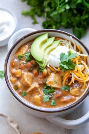 A bowl of chicken chili with cilantro and sour cream in the background.