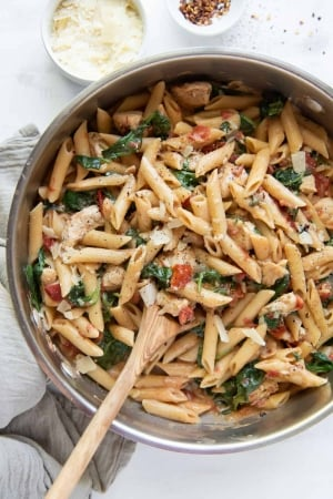 A skillet of pasta with a wooden spoon shot from over the top.