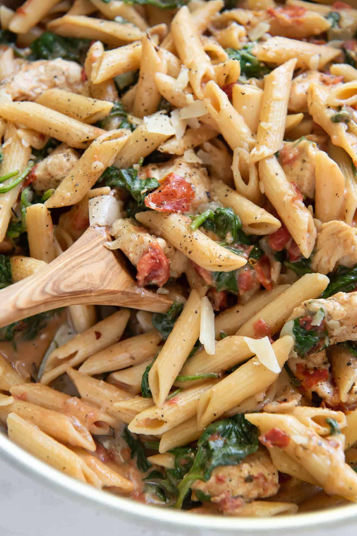 A close up of a spoon in a bowl of pasta with tomatoes, spinach and chicken.