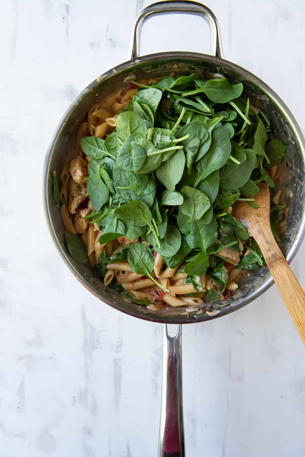 Baby spinach piled on top of pasta in a skillet.