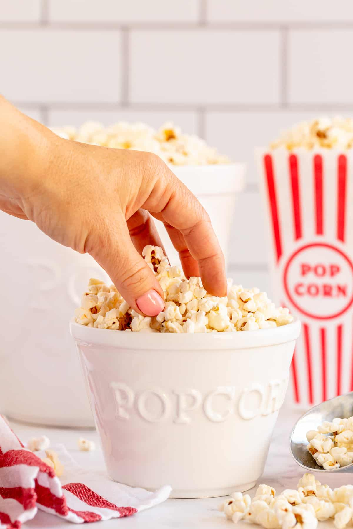 A hand reaches for popcorn from a white popcorn bowl.