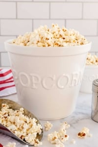 A metal scoop and a tall white bowl filled with popcorn.
