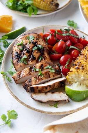 Sliced grilled chicken on a plate with cherry tomatoes and corn.