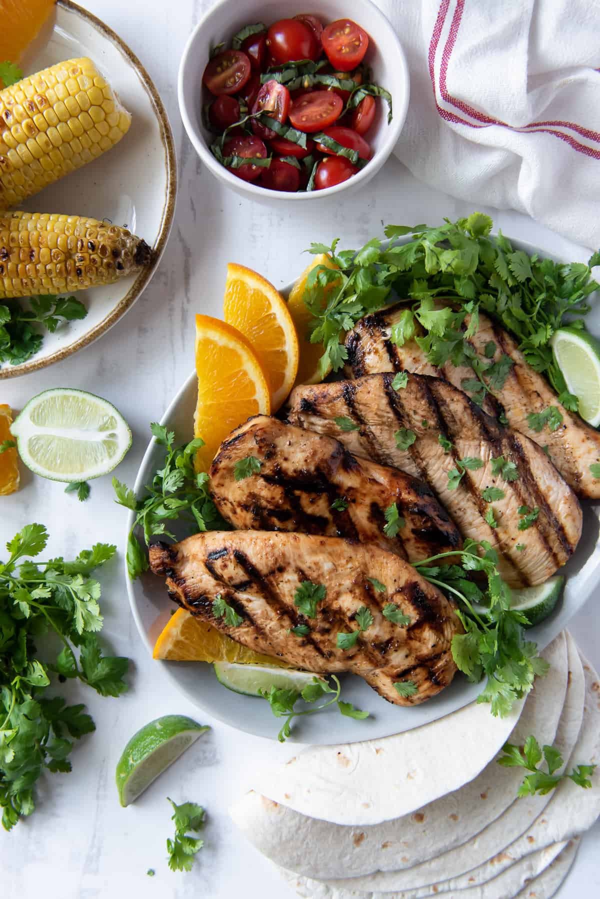 A platter of grilled chicken with cilantro and oranges shot from over the top.
