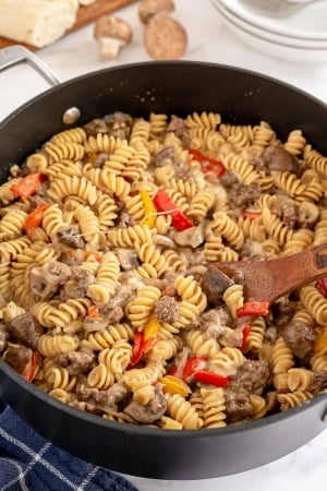 A skillet full of fusilli pasta with ground beef and peppers.