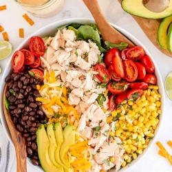 A salad with chicken, avocado, black beans, corn, and tomatoes shot from over the top.