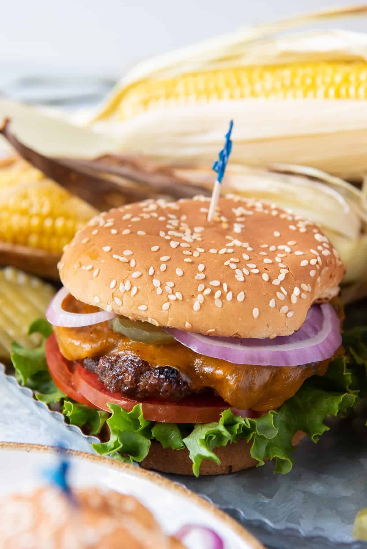 A cheeseburger with onions, tomatoes and lettuce on a sesame seed bun.