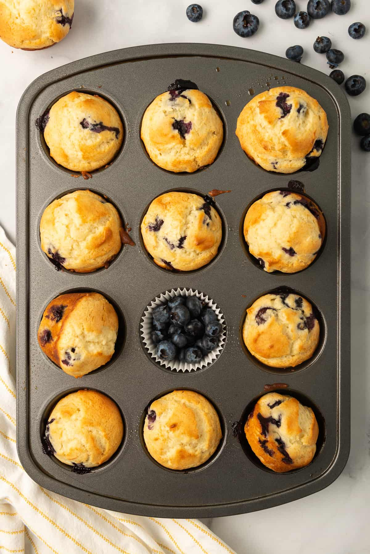 A muffin tray filled with blueberry bread and fresh berries.