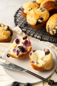 A blueberry muffin cut in half and topped with butter.