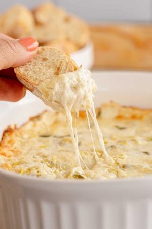 A hand dips a slice of bread into Cheesy Artichoke Dip.