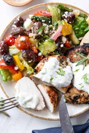 Sliced Greek Chicken with Tzatziki on a plate with colorful Greek salad.