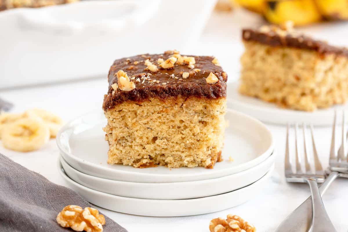 A slice of Banana Cake on a stack of white plates.