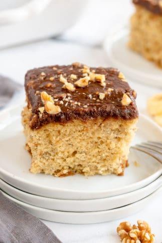 A closeup of a slice of Banana Cake with Chocolate Walnut Glaze on a white plate.