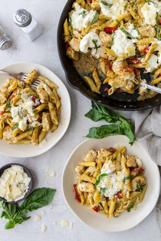 Two bowls of Chicken Pesto Pasta next to a skillet.