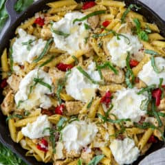A cast iron skillet filled with pasta topped with scoops of ricotta cheese.