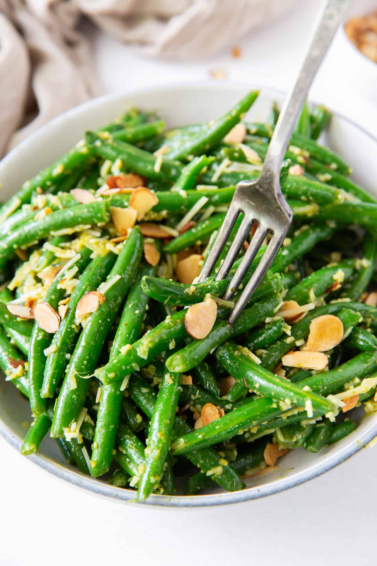 A fork digs into a bowl of Pesto Green Beans.