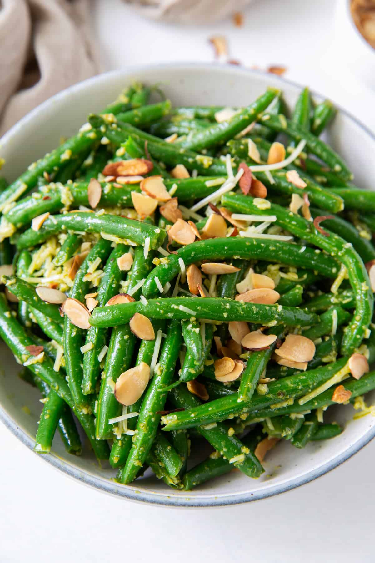 A closeup of a bowl of green beans with pesto, parmesan and toasted sliced almonds.