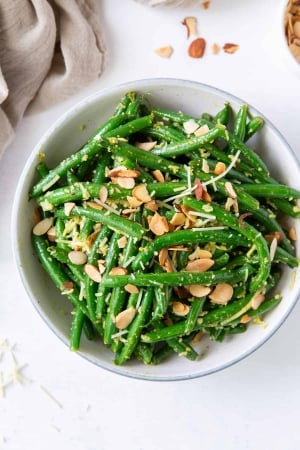 An over the top shot of Pesto Green Beans with almonds next to a grey cloth.