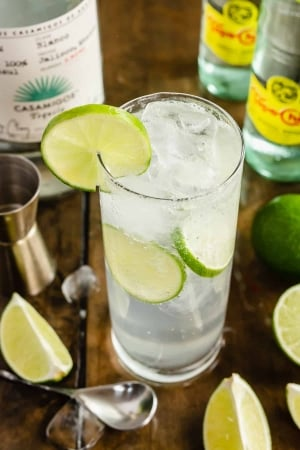 A Ranch Water cocktail in a tall glass with ice and lime slices.