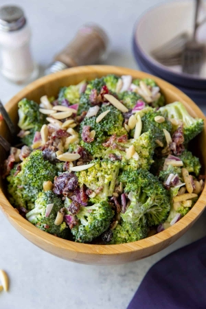 A wooden bowl full of Broccoli Salad with salt and pepper shakers in the background.